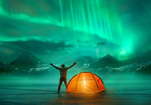 Man outside of his tent looking at a green aurora with his arms open